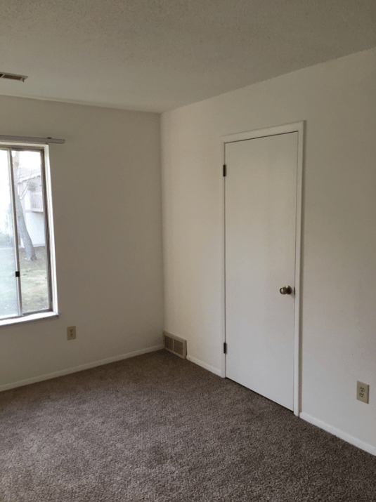 a picture of a white door in an empty room after a commercial water damage project